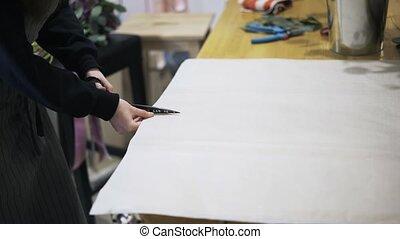 Woman florist cutting paper sheet with scissors on desk