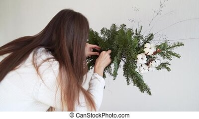 Woman florist doing pine garland for christmas in slow motion. DIY decoration, small business. High quality FullHD footage