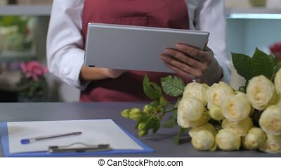 Woman florist hands using tablet for taking orders -...