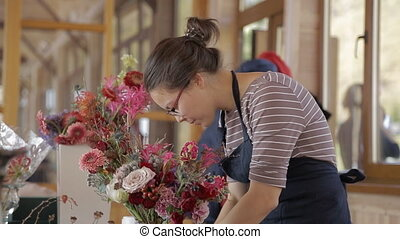 Woman florist in an apron adorns bouquets with sequins for event.