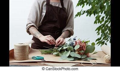 Woman florist in apron near table creates flower arrangement...
