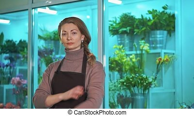 Woman florist is looking at the camera, on the background of a showcase of flowers.
