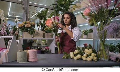 Woman florist making bunch of flowers at workshop - Young...