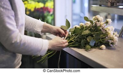 Woman florist threading a bunch of white roses - Close up of...