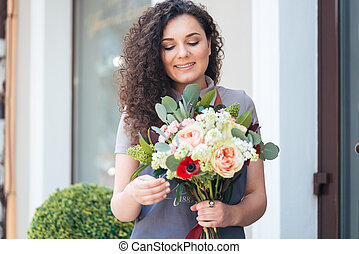 Woman florist with flower bouquet standing in front of shop