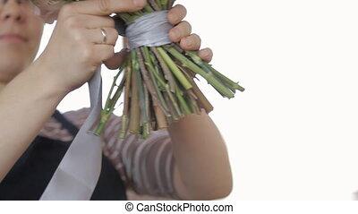 Woman florist wraps bouquet with satin ribbon in workshop.