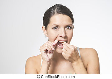 Woman flossing her teeth with dental floss to remove any...