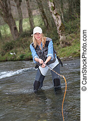 Woman fly-fishing in river