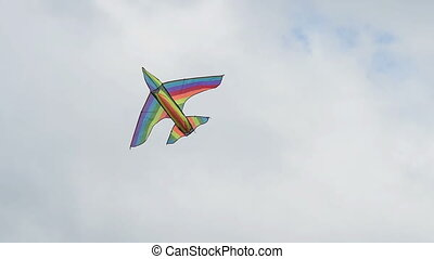 Woman flying a kite - Woman flying rainbow kite, view to two...