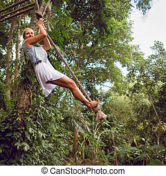 Woman flying high on rope swing on wild jungle background