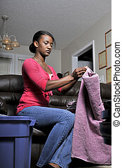 Woman Folding Clothes - A young African American woman ...