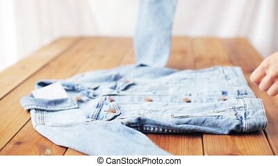 woman folding denim jacket on wooden table at home -...