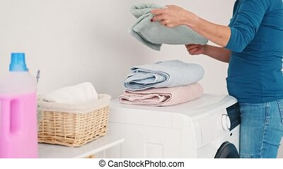 Woman folding fresh clean towels in stack after washing indoors