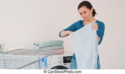Woman folding fresh dried towels taking from dryer in laundry room