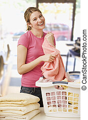 Woman Folding Laundry - A young woman is folding laundry and...