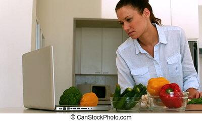 Woman following recipe on laptop in slow motion