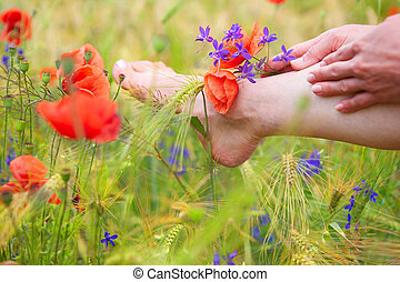 Woman foot among the green plants and poppy