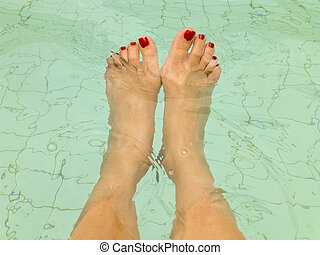 Woman Foots in the Water of a Swimming Pool