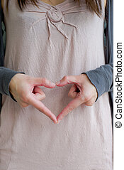 woman forms heart with hands