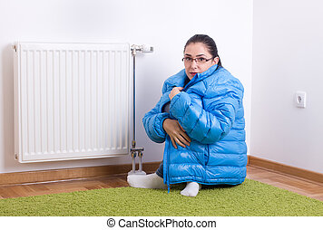 Woman freezing next to radiator - Young woman in blue winter...