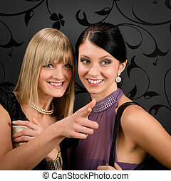 Woman friends party dress point at smiling