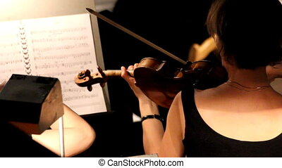 woman from behind playing on violin in orchestra
