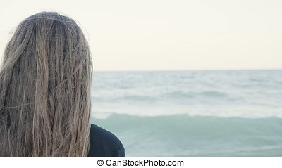 Woman from the back looking away at the sea - Slow motion of...