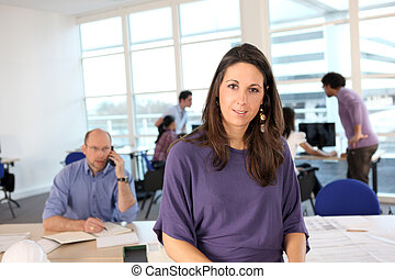Woman fronting a busy office