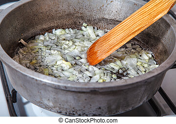 woman frying onions in the frying pan closeup
