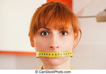 Woman gagged by a tape measure - symbol for eating disorder