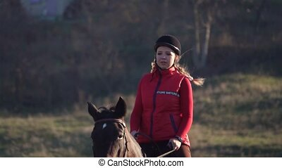 Woman galloping on a green field on horseback. Slow motion
