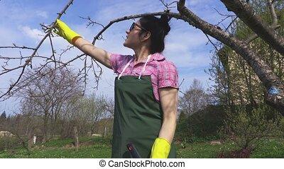 Woman gardener near apple tree