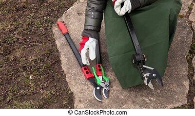 Woman gardener take branch cutter and scissors