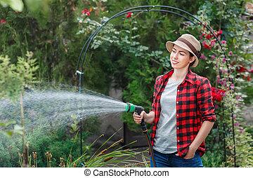woman gardener watering garden - happy young woman gardener...