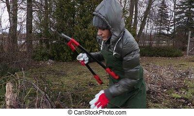 Woman gardener with scissors near branch pile