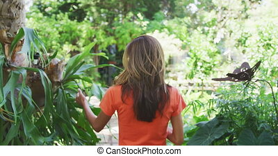 Woman gardening in nature - Rear view of a Caucasian woman ...