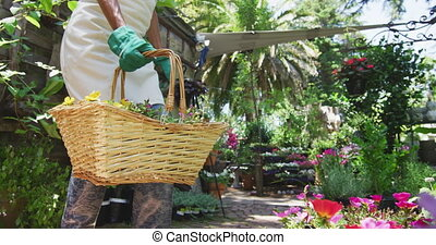 Side view mid section of a Caucasian woman wearing an apron and gardening gloves kneeling in a sunny garden, picking up a basket with a selection of plants in it and walking away, in slow motion