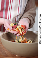 Woman gathering vegetable peelings