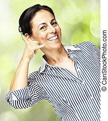 woman gesturing telephone