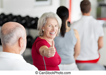 Woman Gesturing Thumbs Up Sign With Family Sitting In Gym -...