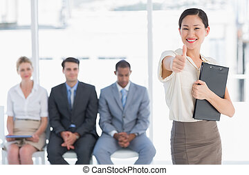 Woman gesturing thumbs up with people waiting for interview