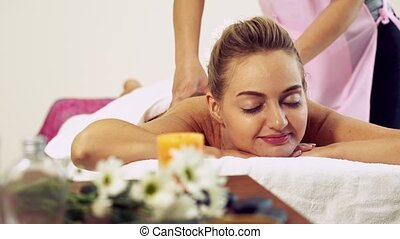 Woman gets back massage spa by massage therapist. - Relaxed ...