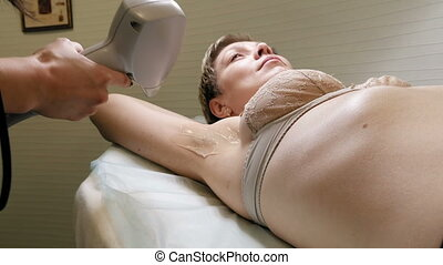 Woman gets laser hair removal treatment underarm. Modern...