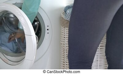 Woman gets laundry from washing machine - Woman takes out...