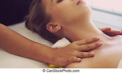 Relaxed woman getting shoulder massage in luxury spa by professional massage therapist. Wellness, healing and relaxation concept.