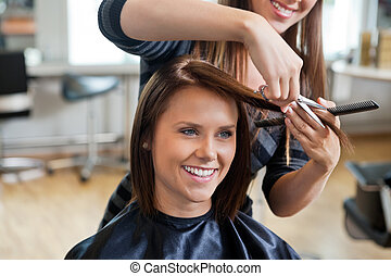 Woman Getting a Haircut - Happy young woman getting a new...