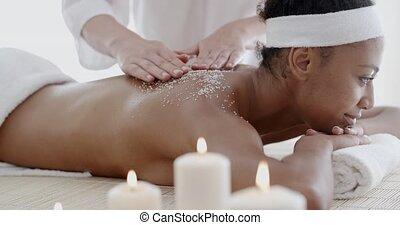 Woman Getting A Salt Scrub Treatment - Woman getting a salt...