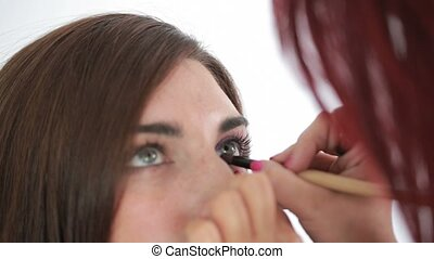 Woman with pink lips getting applied cat eyes