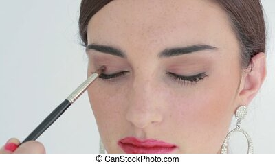 Woman getting applied red lips and