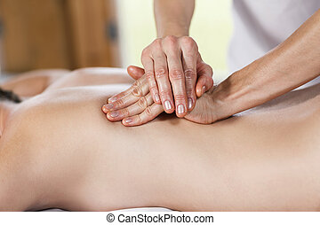 Woman getting back massage at spa